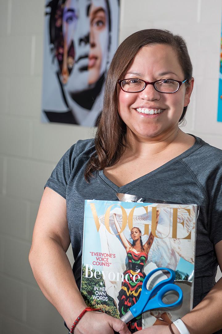 Student poses holding Vogue magazine.