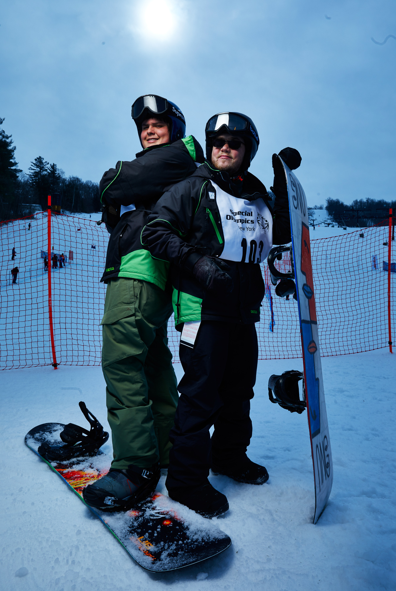 Two snowboarders stand back to back