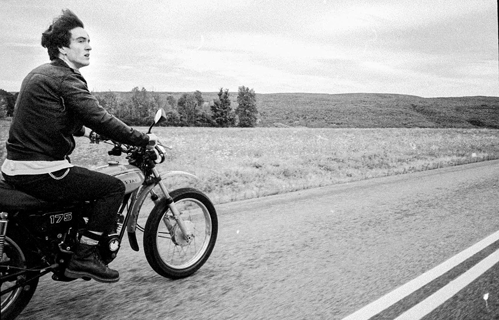 A black-and-white photo of someone riding a motorcycle on an open highway.