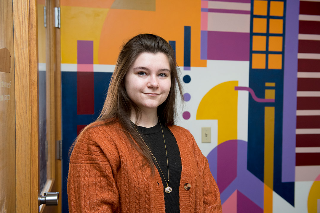 student posing in front of abstract wall mural.