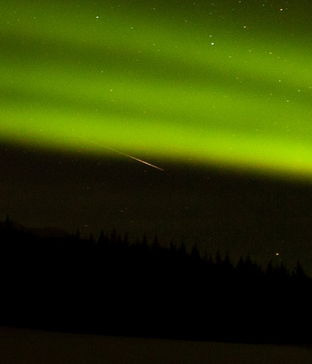 Green Northern Lights over mountains.