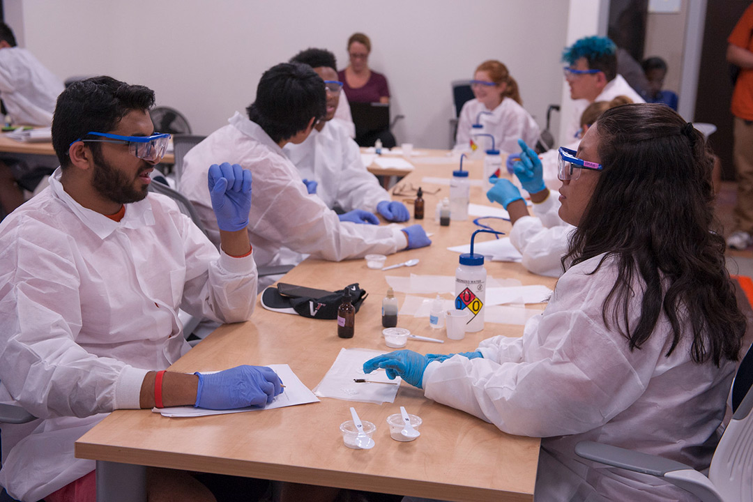 Students in lab coats working at a table.