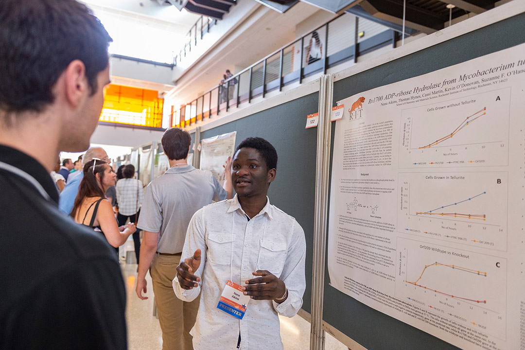 Student gives poster presentation.
