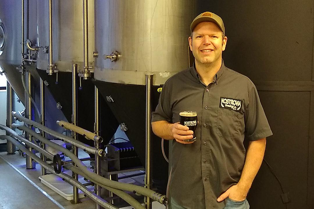 man standing next to vat of beer.