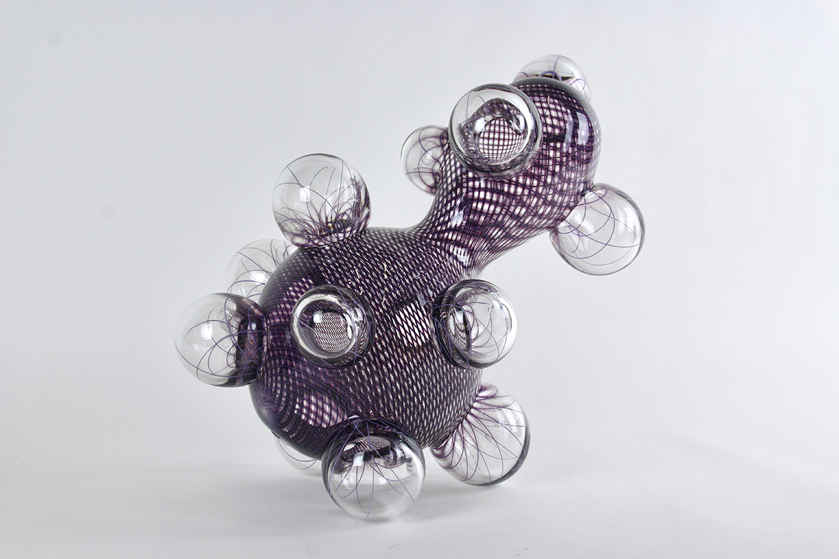 A purple glass work with spheres all around it.
