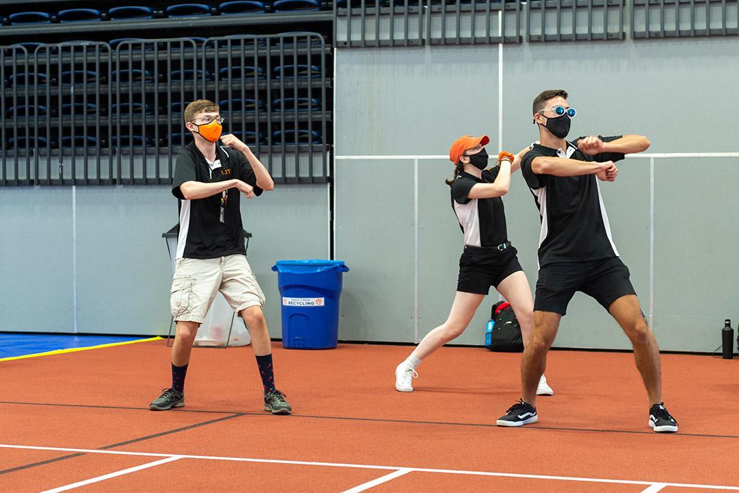 three students wearing masks and dancing.