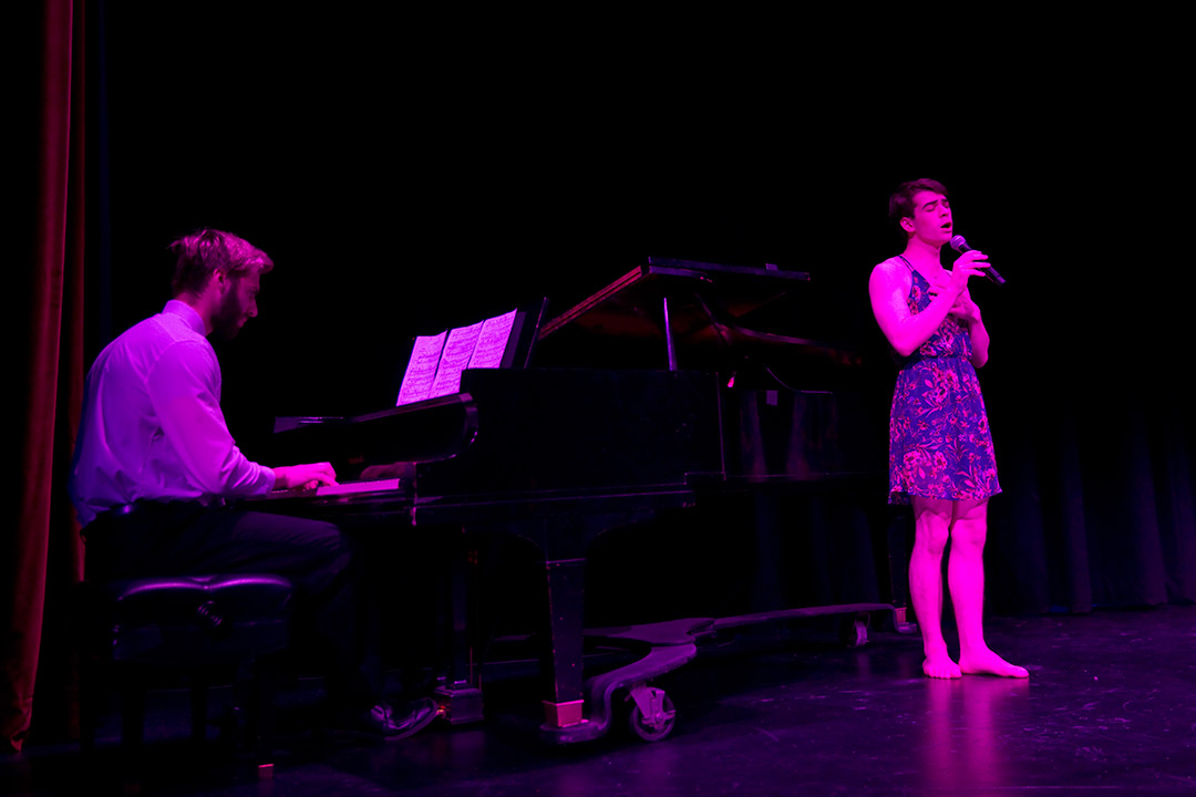 Singer performs while another plays the piano.