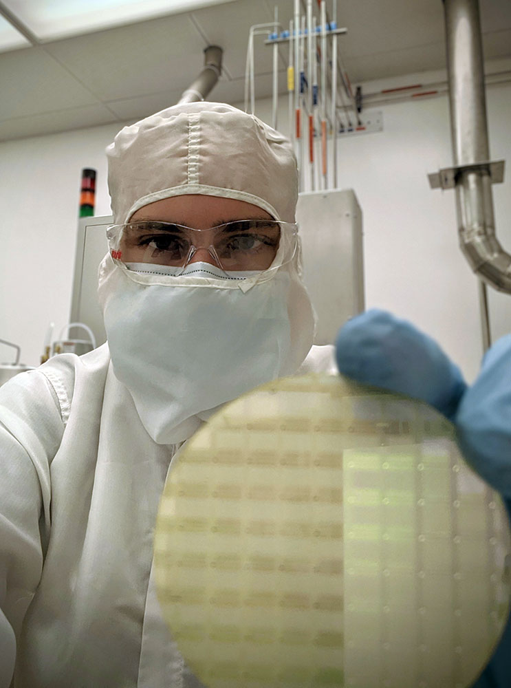 lab technician wearing clean suit and holding a silicon wafer.