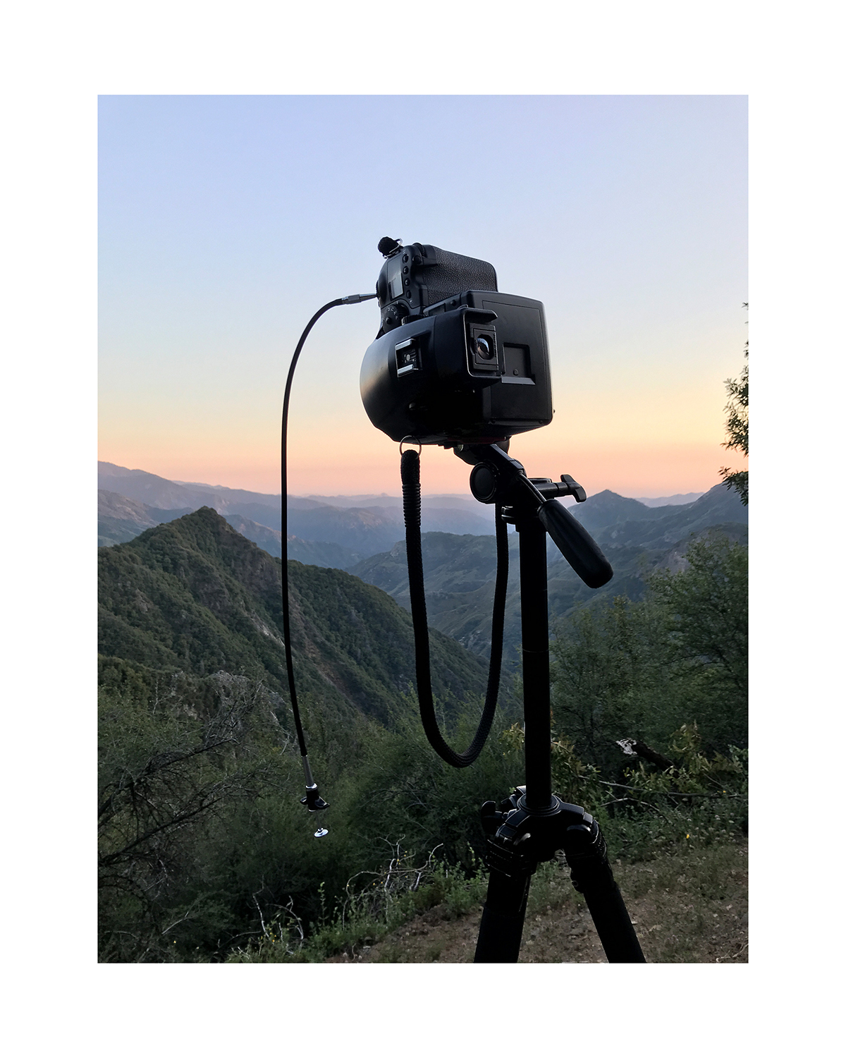 A photo of a video camera set against a mountainous background.