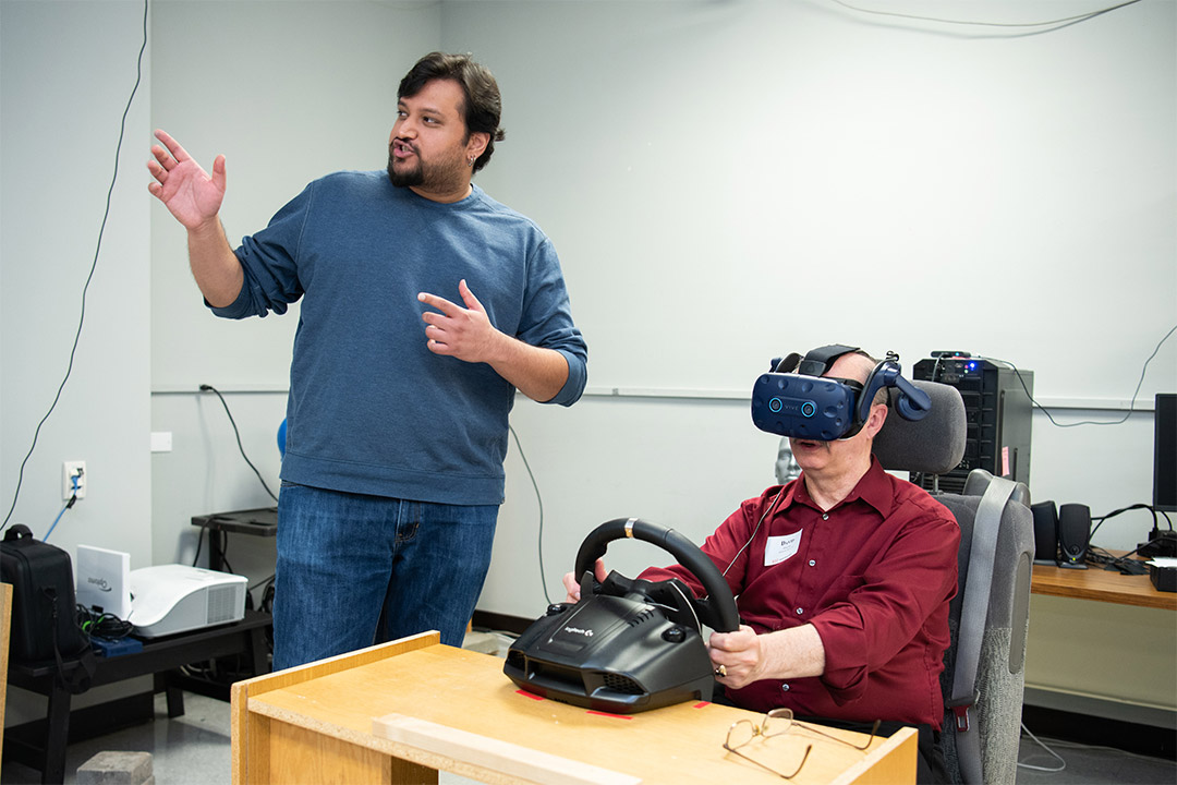 Man wears VR goggles while sitting at table holding a steering wheel.