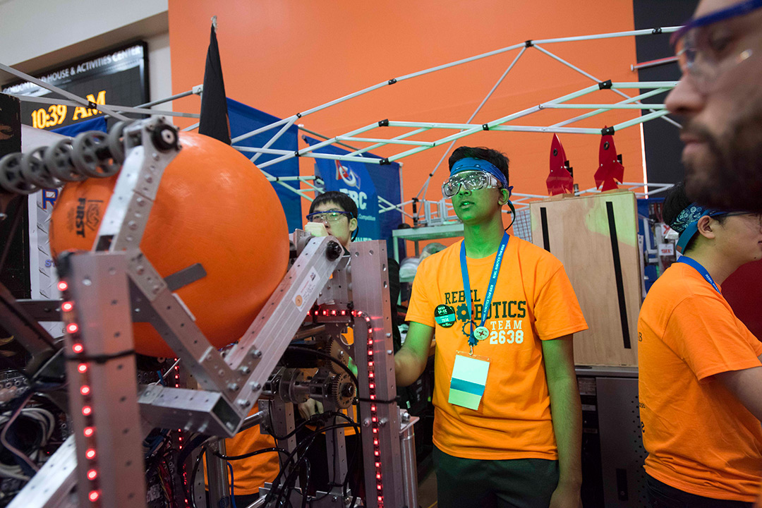 Student in orange T-shirt controls robot holding giant ball.