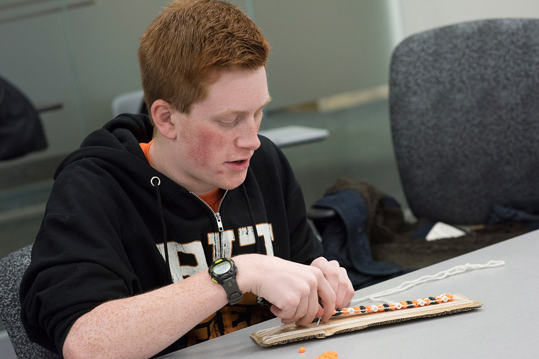 Student makes wampum belt with beads.
