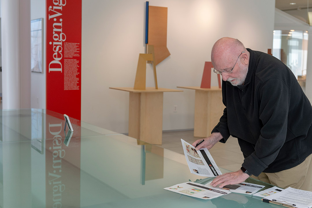 retiring professor looking at printouts on glass table.