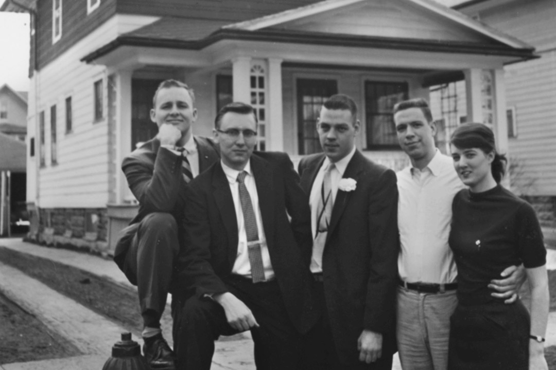 group of five people standing outside of house in 1959.