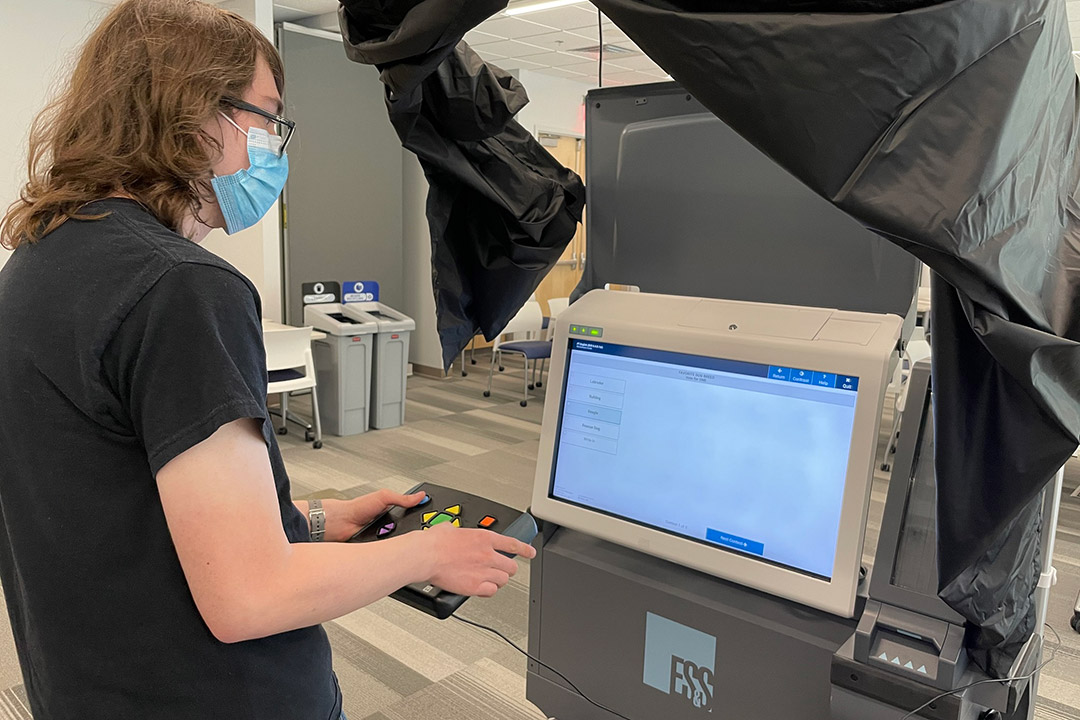 student testing a computer voting machine.