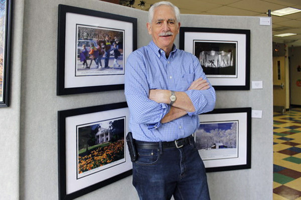 Man poses in front of framed photos.
