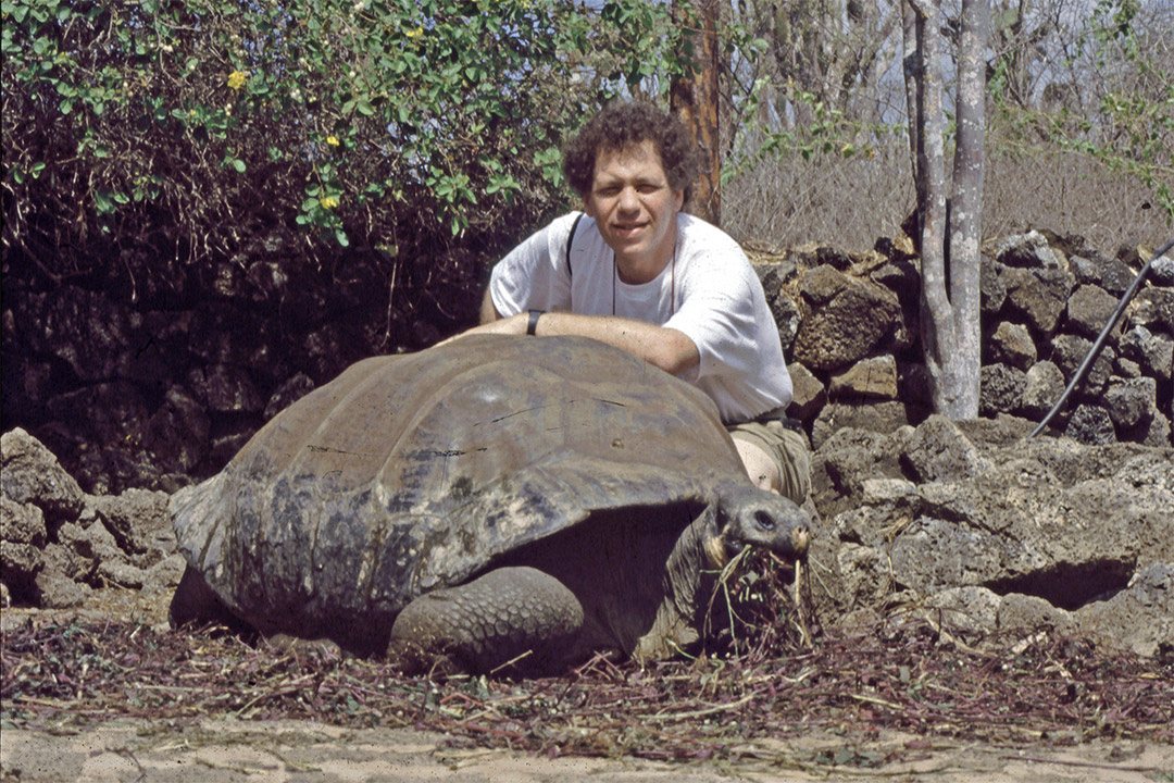 man posing with a giant tortoise in 1989.