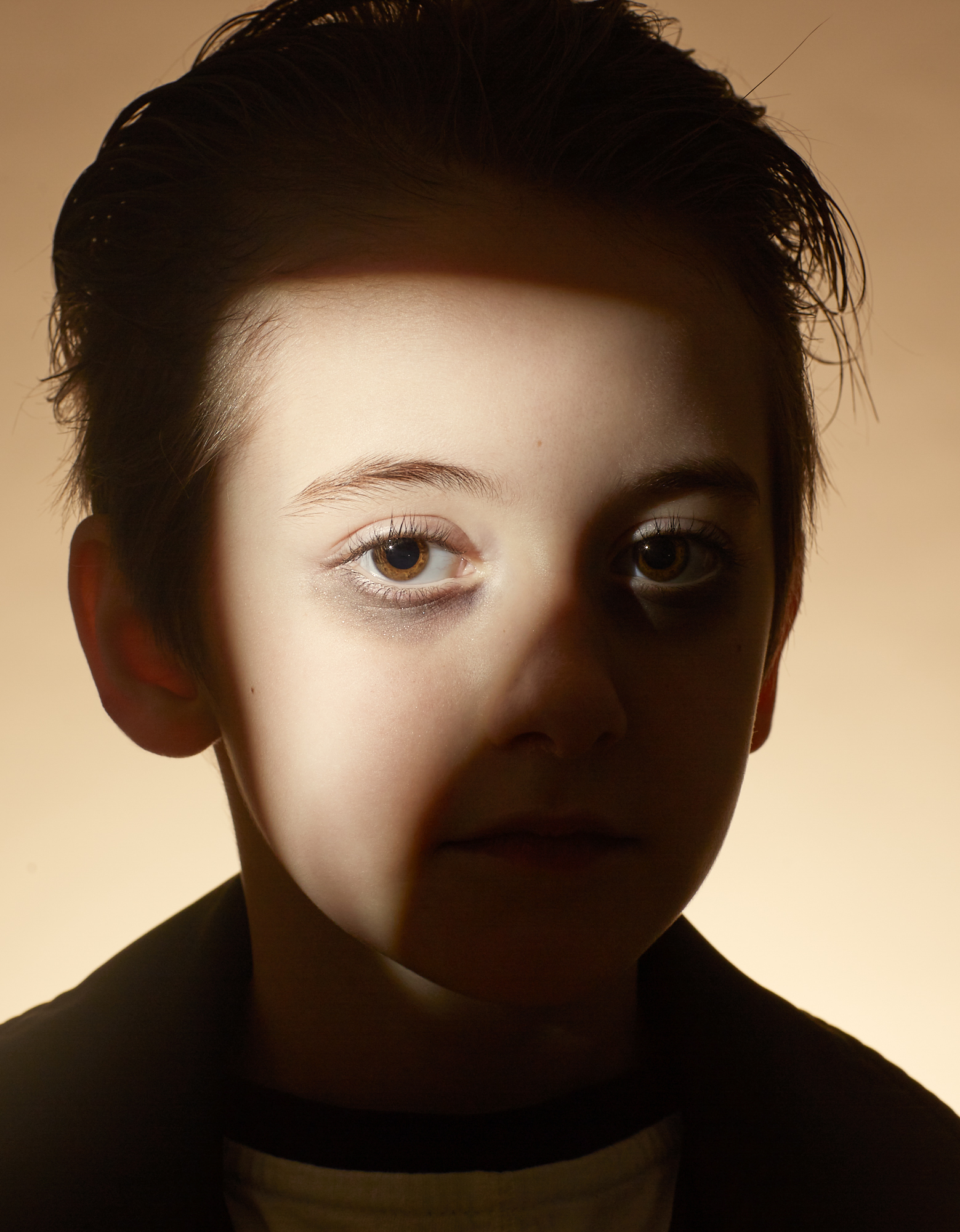 Portrait photography of a boy with light shining on part of his face.