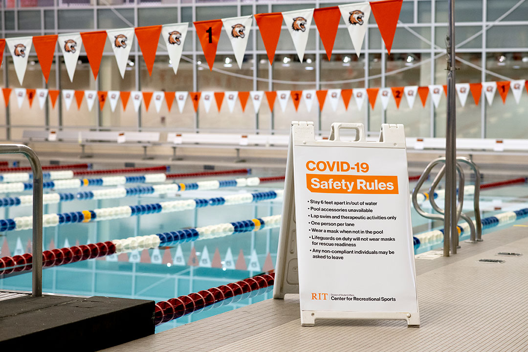 sign with COVID-19 Safety Rules next to indoor swimming pool.