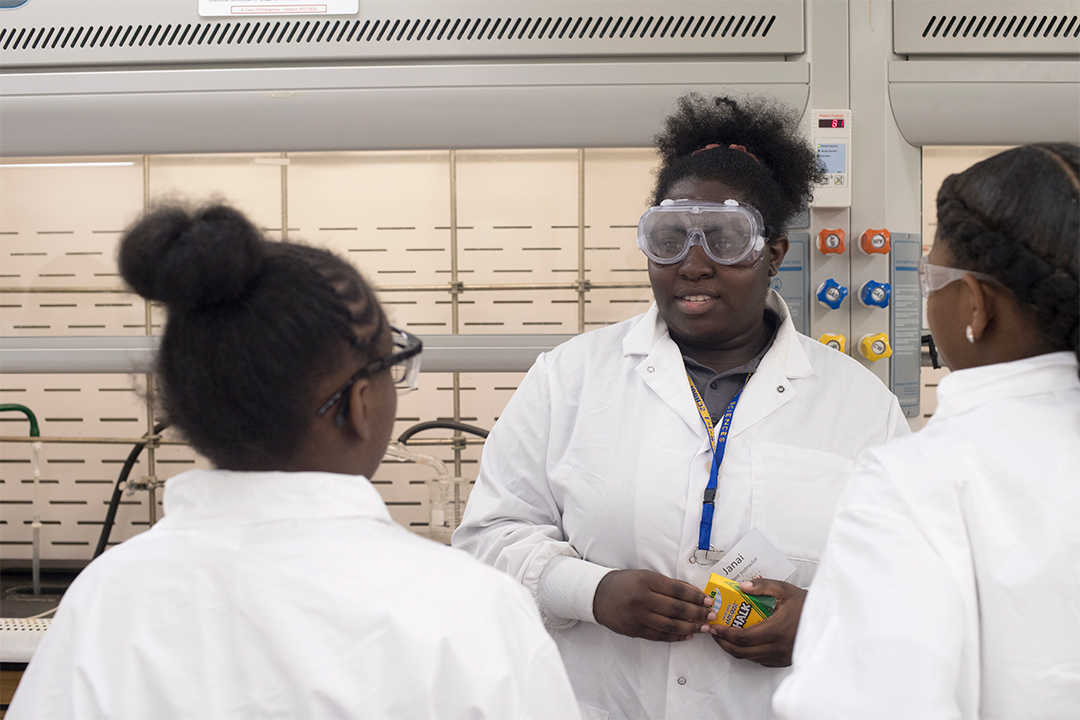 Students in lab coats talk to each other.