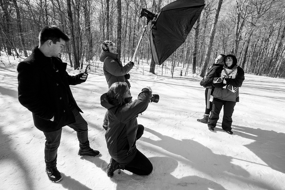 Students photograph athletes participating in the Special Olympics Winter Games.