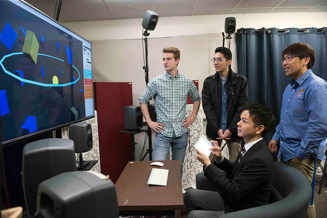 Students and researchers sit and stand around TV screen displaying geometric shapes