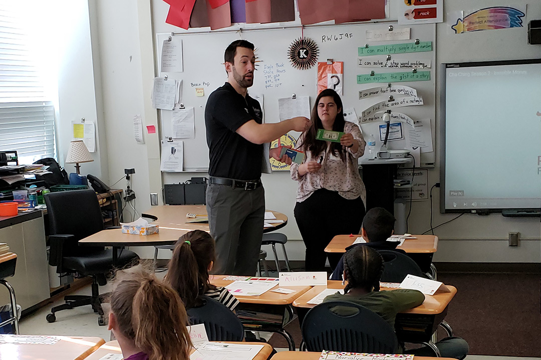 Alumnus and student teach elementary school children.