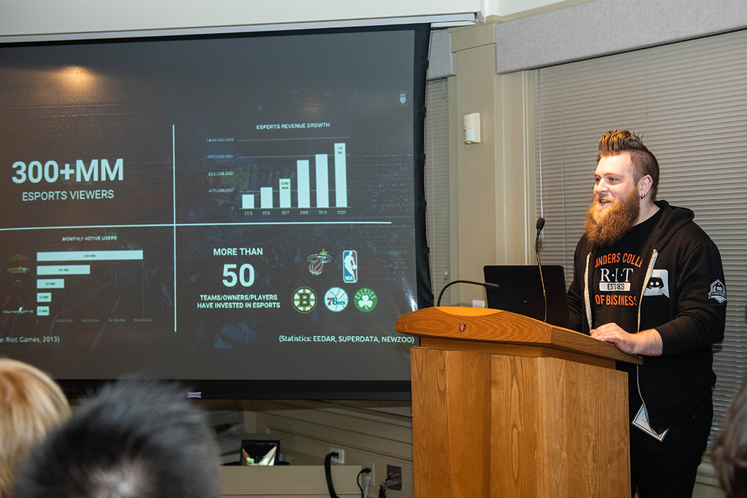 Man stands at podium with PowerPoint presentation displayed on screen next to him