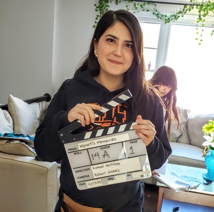 Selma Pena holding a clapperboard on a film set.