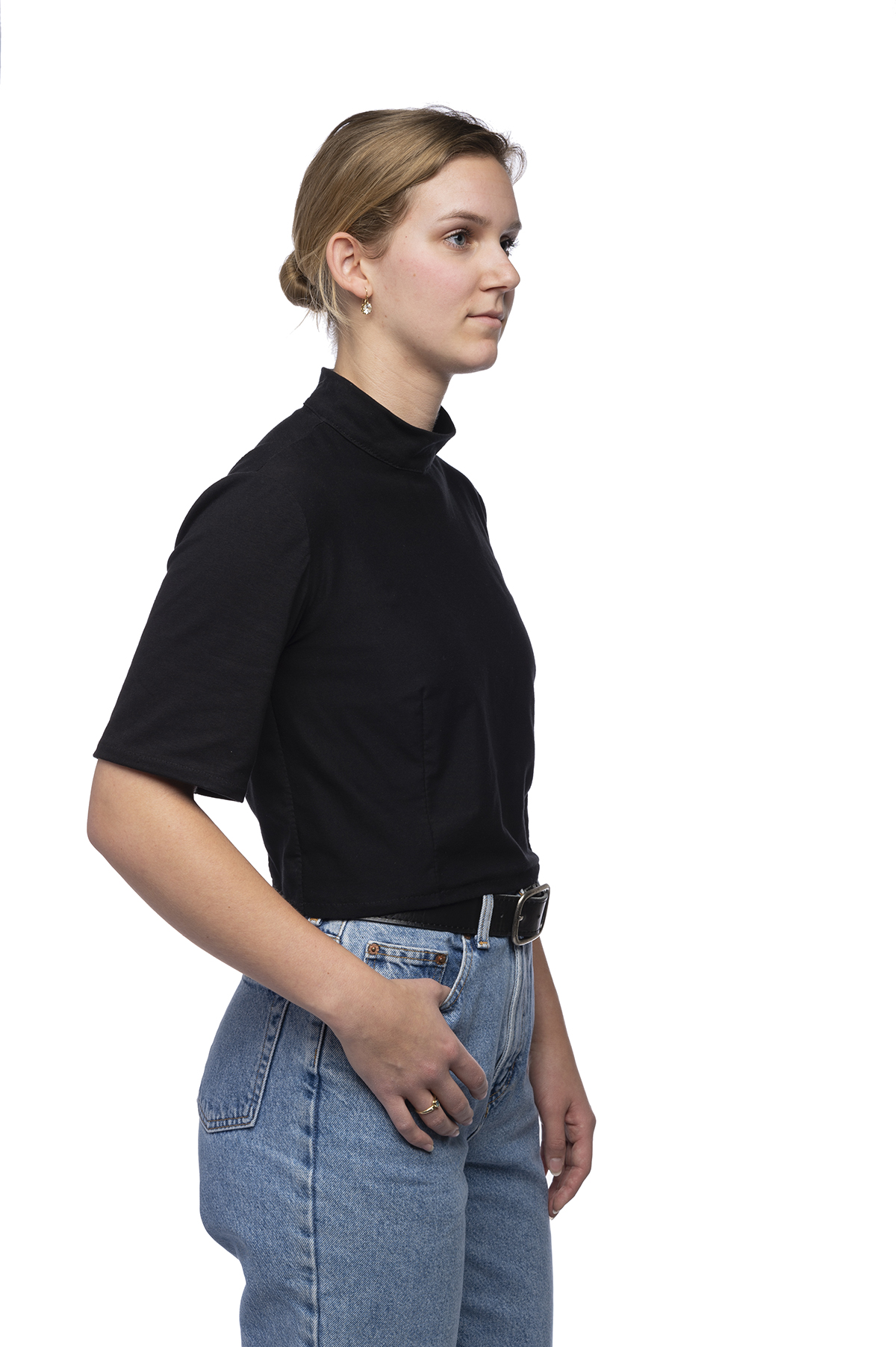 Functional clothing design of a black top tucked into denim jeans.