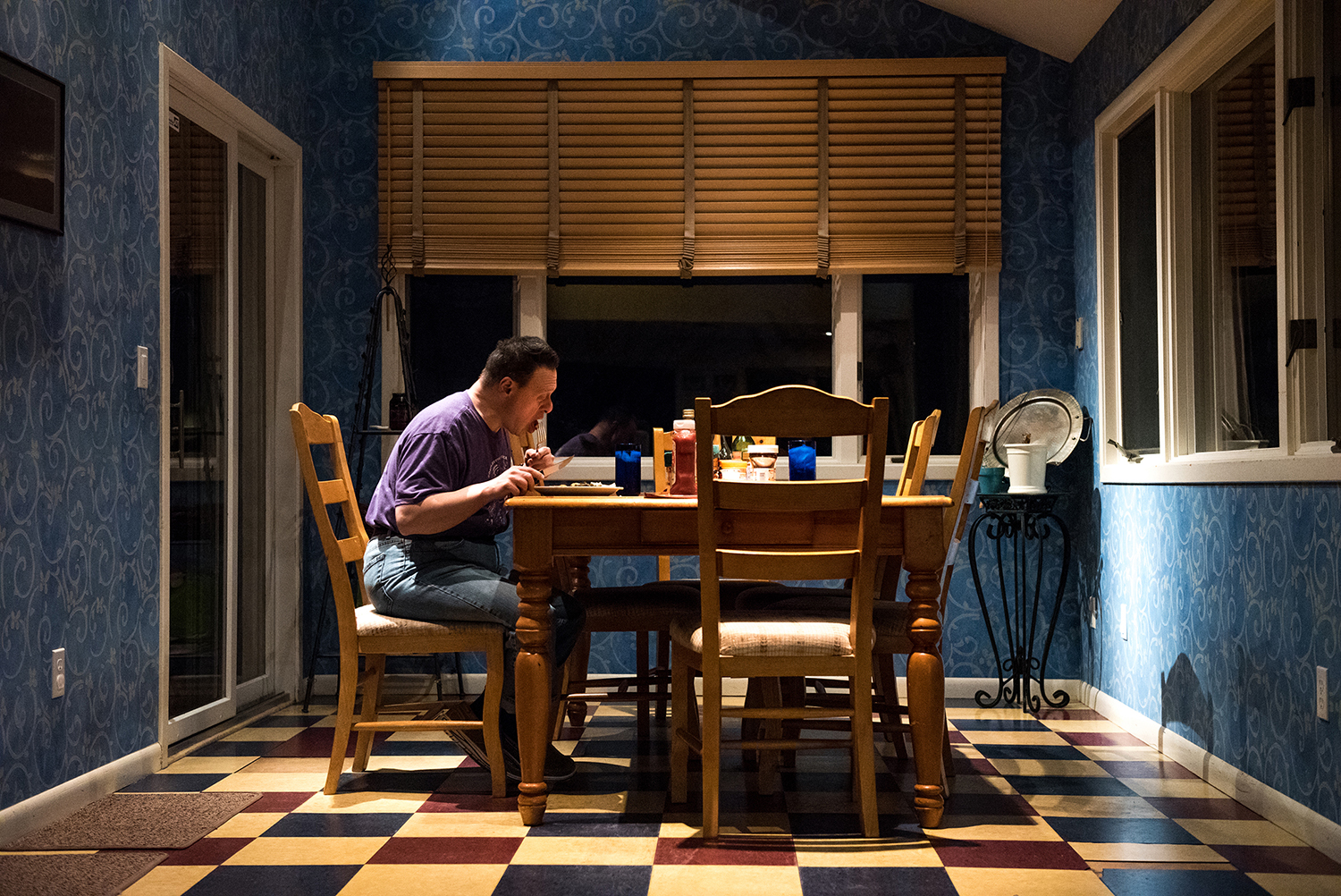 A photo of a man eating at a kitchen table.