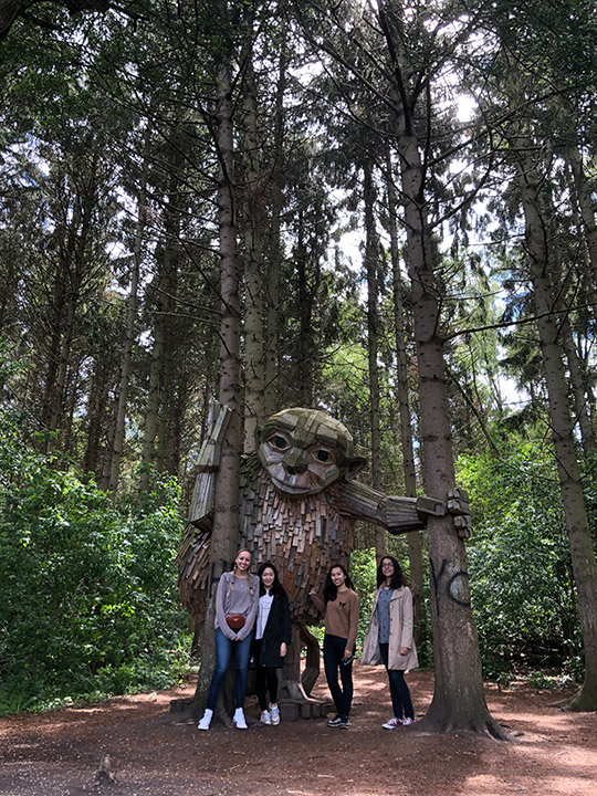 Students stand in forest with statue of giant.