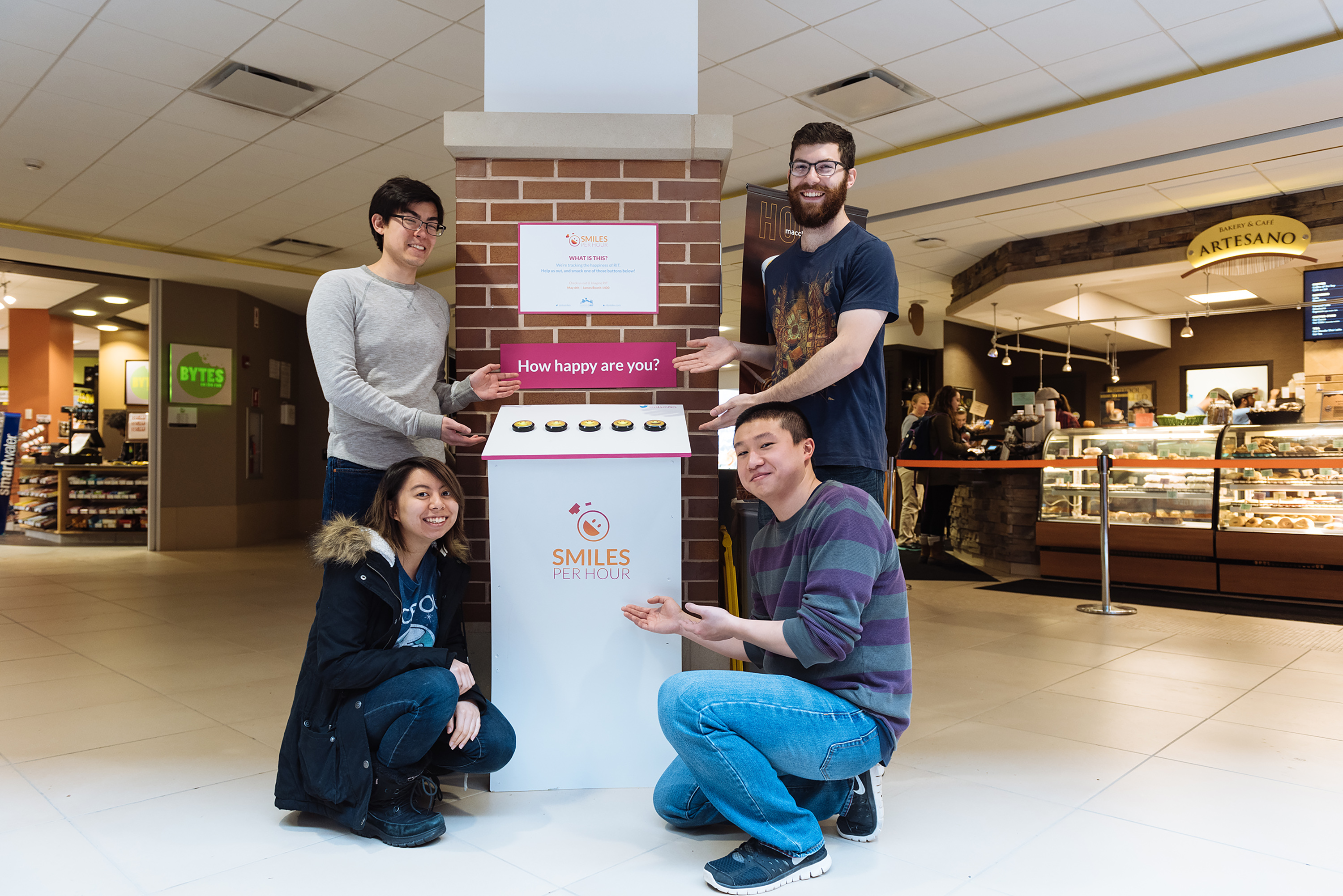 4 people pose next to a white podium in front of Artesanos