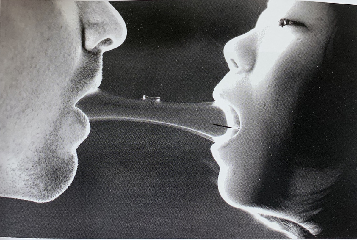 Two people put their mouths on the same glass object.