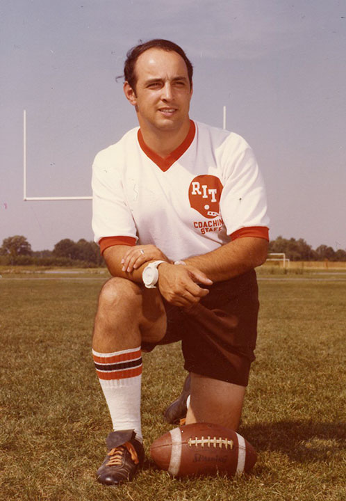 Football player kneels next to ball in 1960s.