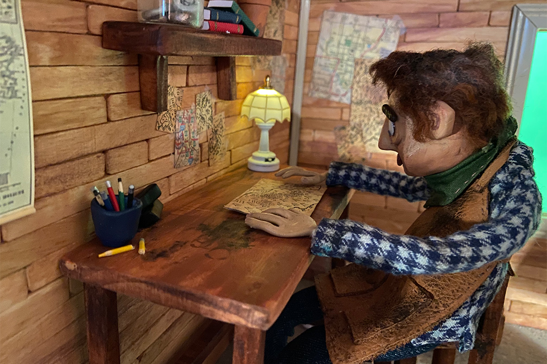 stop-motion scene of a man sitting at a desk looking at a map.