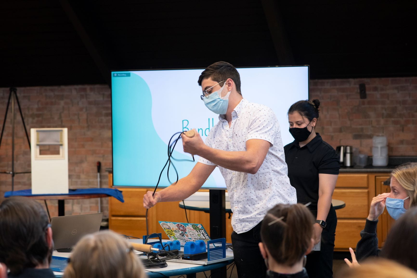 A person in a mask pulls wires from a device