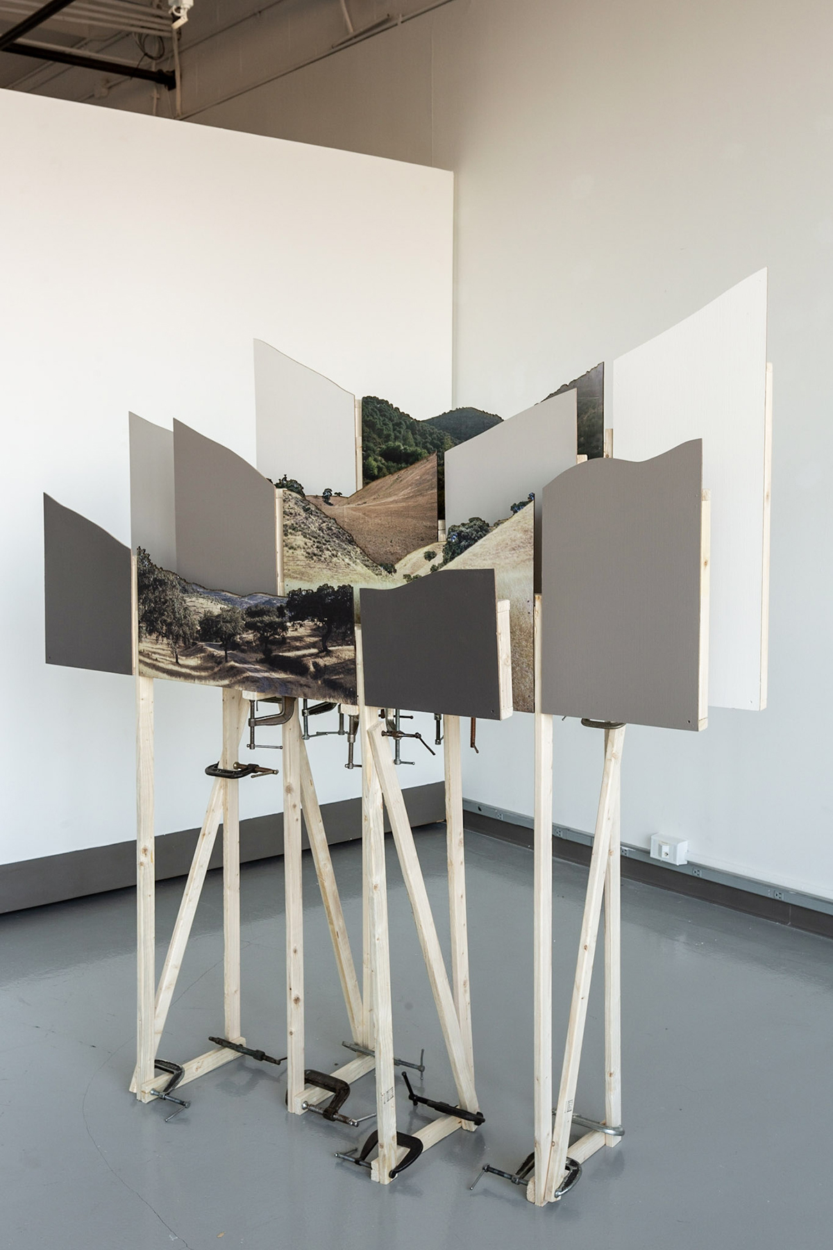 A series of photo prints sits on an intricate easel-type structure.