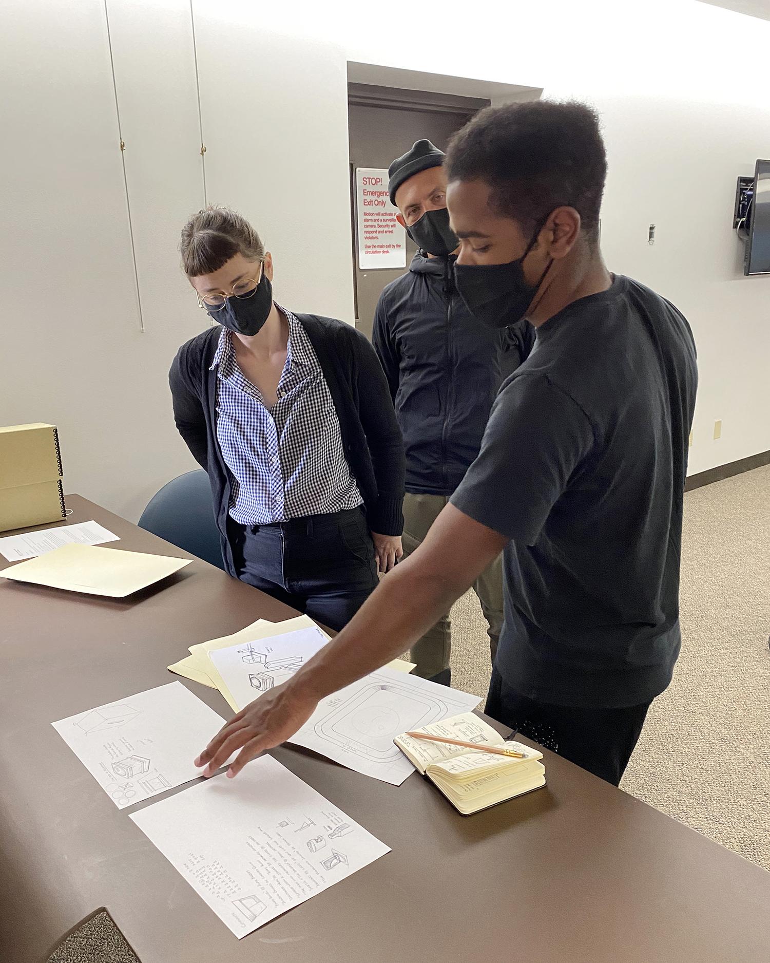 Tiree Walker talks through process sketches with Ella von Holtum and Josh Owen.