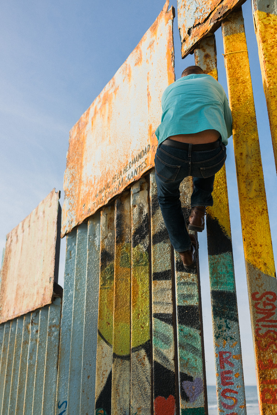 A man climbs a structure covered with art.