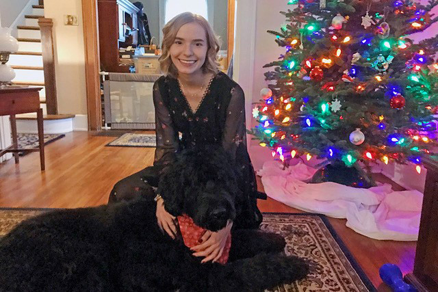 Student sitting on floor with large black dog.