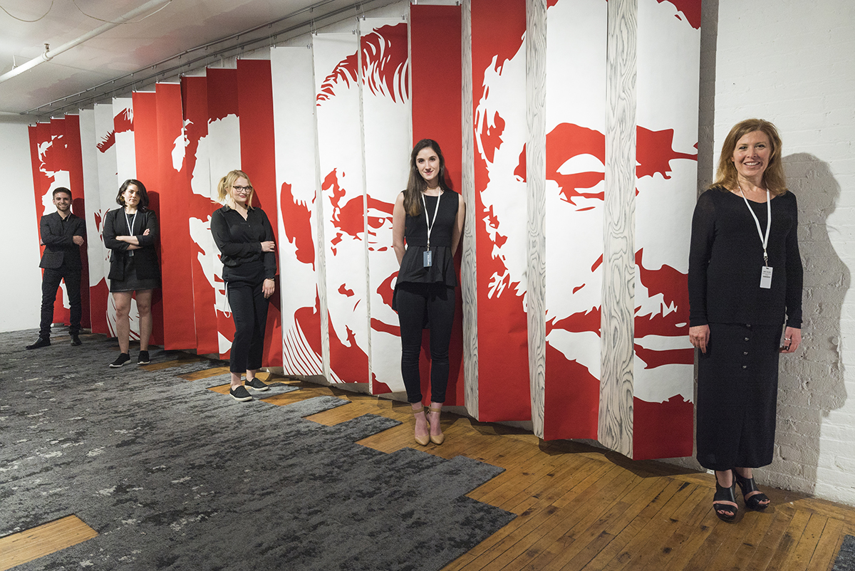 The five RIT interior designers behind Archivio in front of a panel wall they created for the exhibit