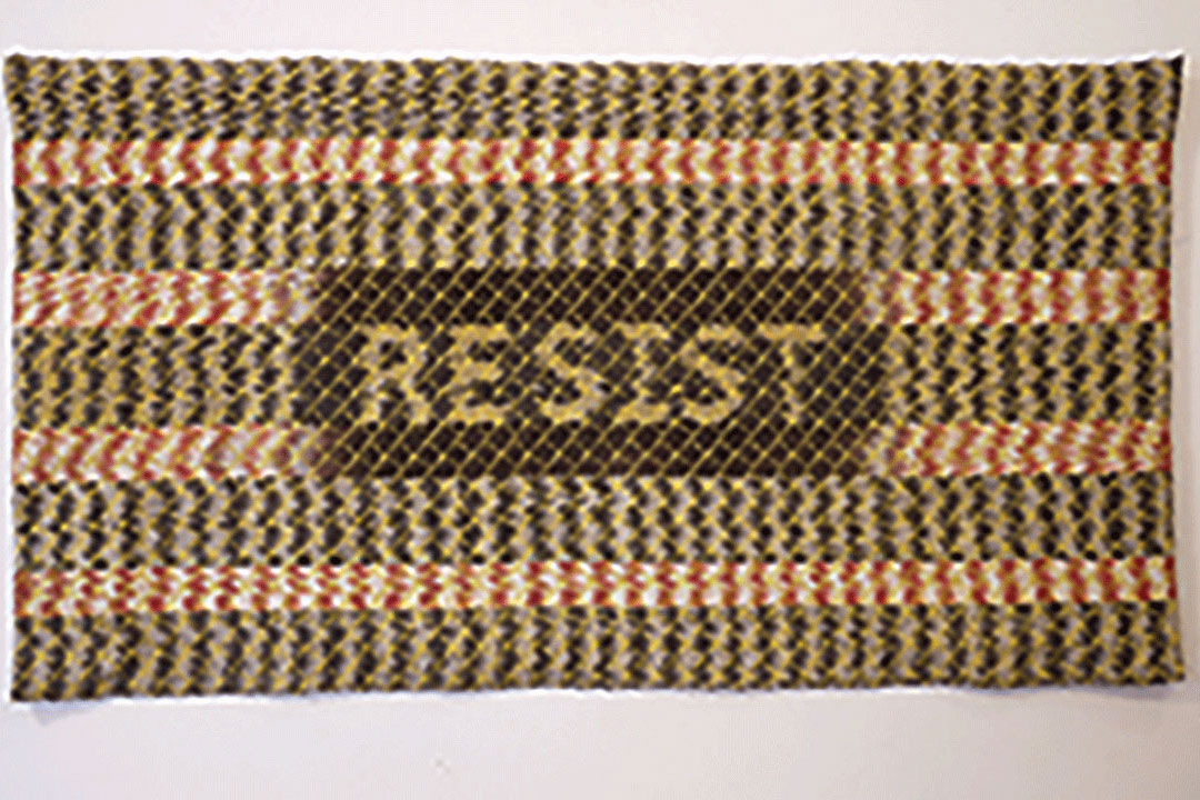 "Knit rug with the word ""RESIST"" in the center."
