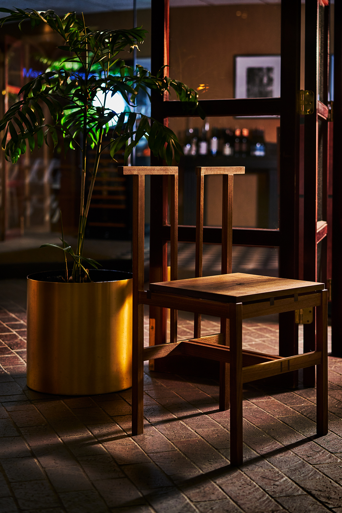 A chair designed by Yichi Cheng next to a plant.