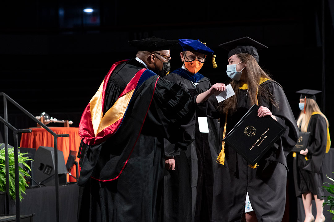Graduate elbow-bumping faculty on stage during graduation.