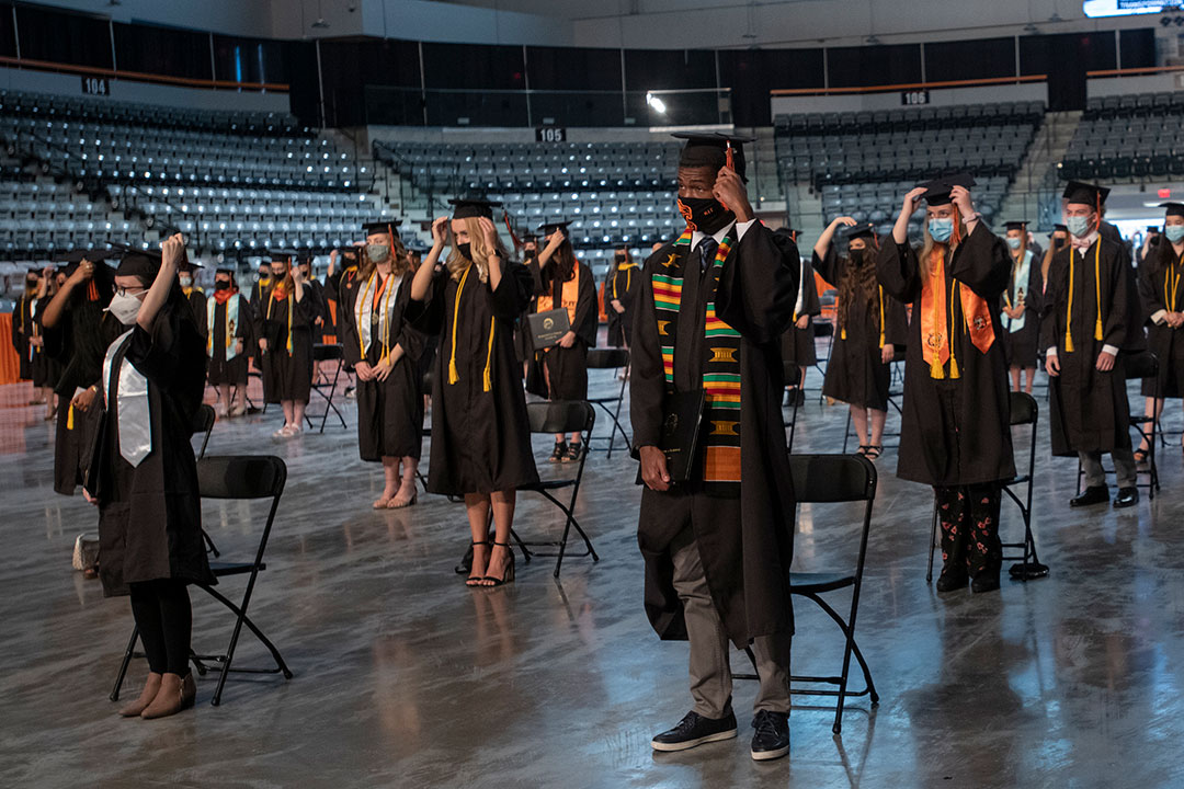 Graduates turn tassel on their graduation caps.
