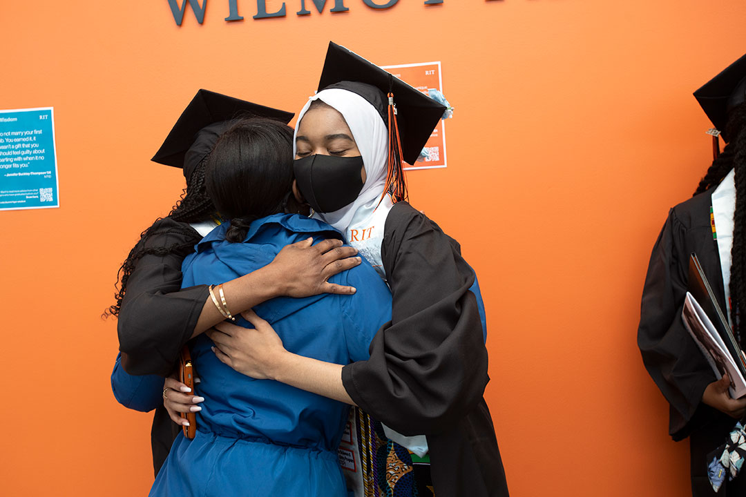 Student wearing graduation regalia hugging a family member.