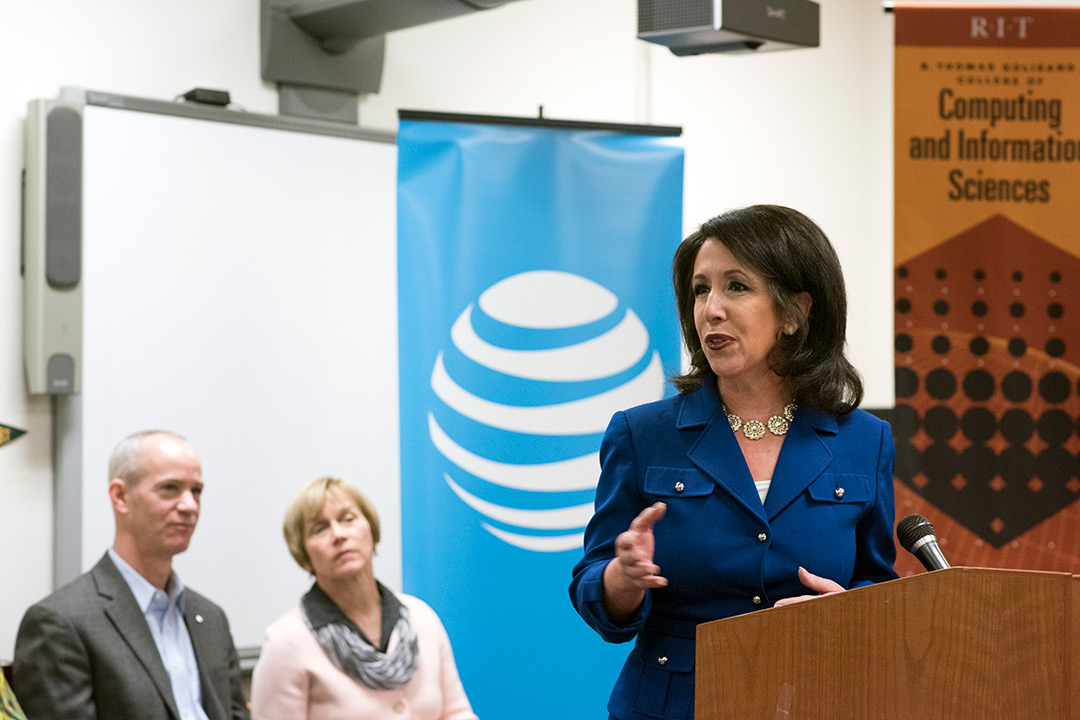 Woman speaks at podium as woman and man in background look on