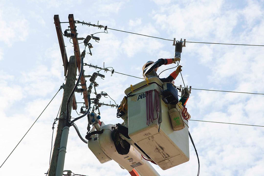worker in cherry picker bucket working on power lines.