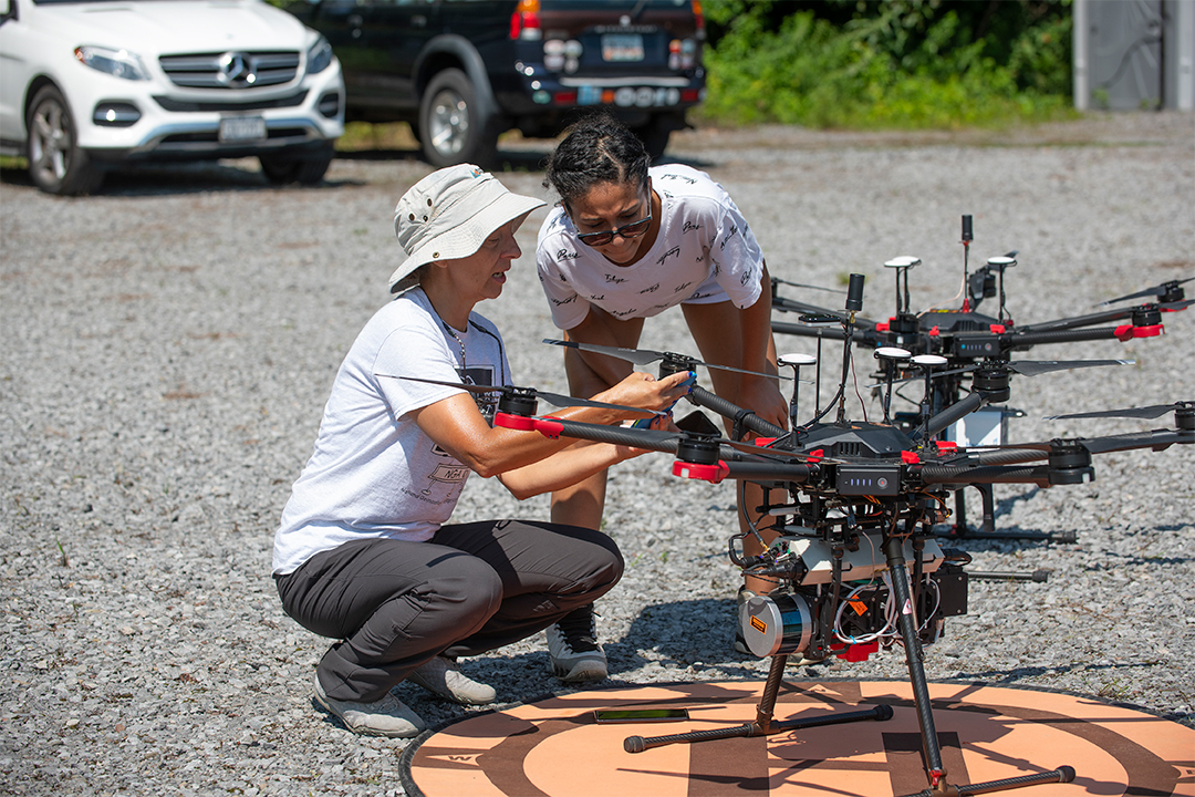 Two researchers work with a drone.